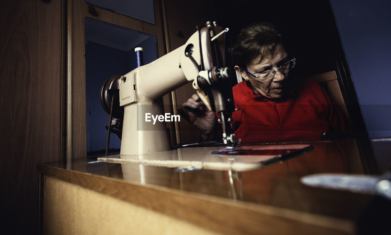 Woman by sewing machine at home