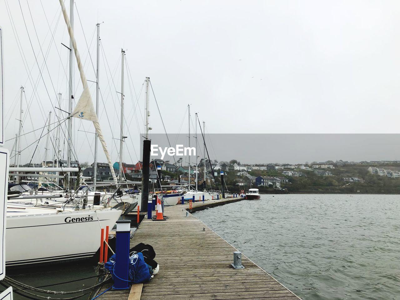 nautical vessel, water, transportation, mode of transportation, sailboat, pole, sky, sea, moored, nature, mast, day, harbor, pier, real people, travel, sailing, outdoors, men, yacht, marina