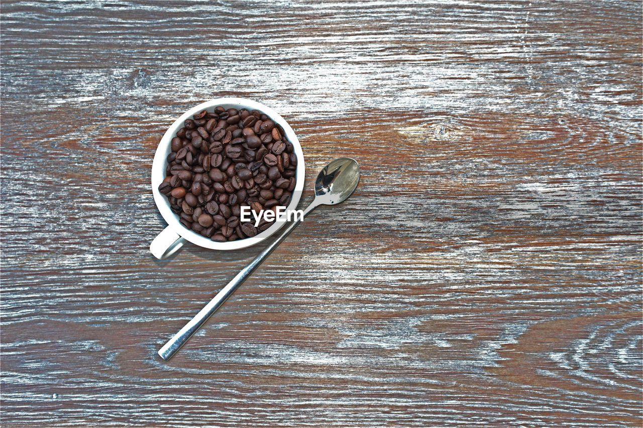 High angle view of roasted coffee beans in cup on wooden table