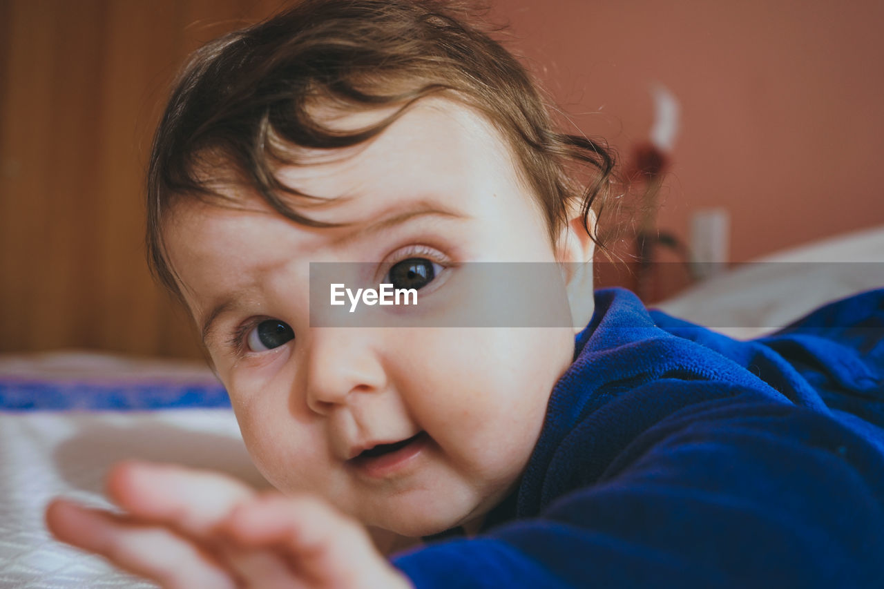 Portrait of cute baby girl on bed at home
