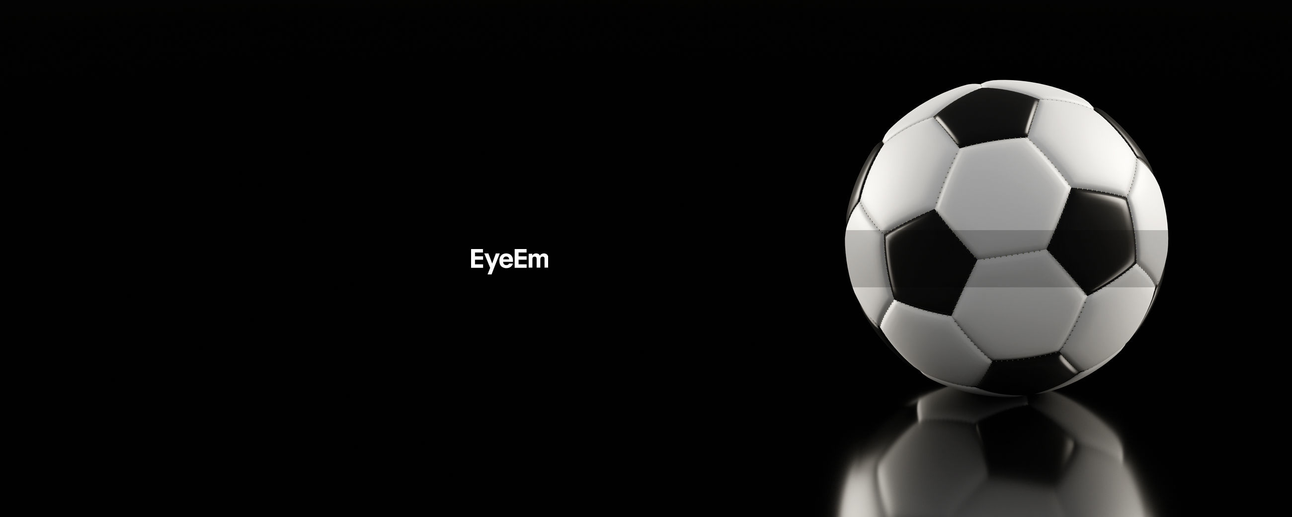 Panoramic view of soccer ball against black background