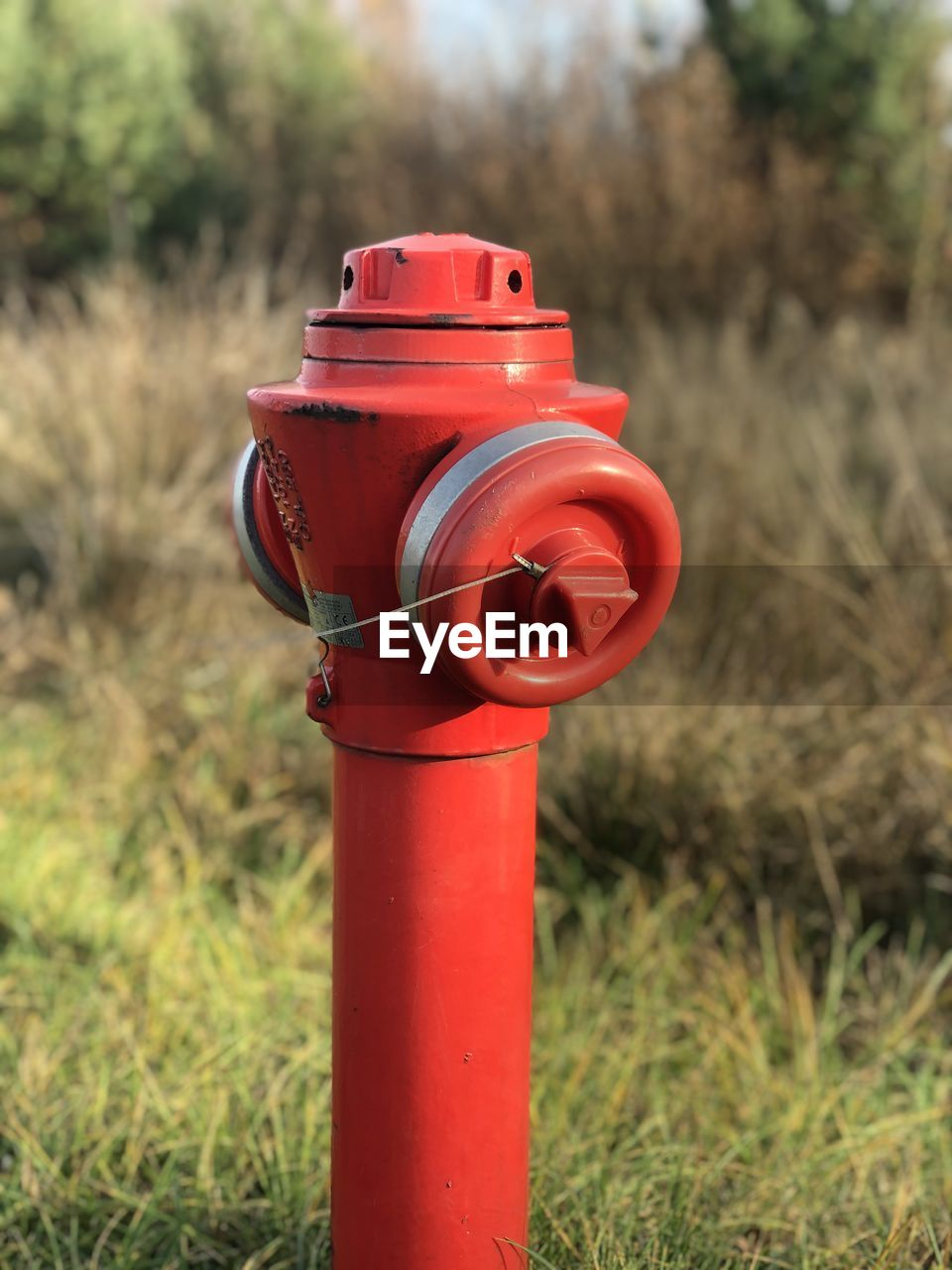 red, focus on foreground, grass, field, day, fire hydrant, metal, safety, land, security, close-up, plant, mail, nature, protection, communication, no people, outdoors, technology, letter, correspondence
