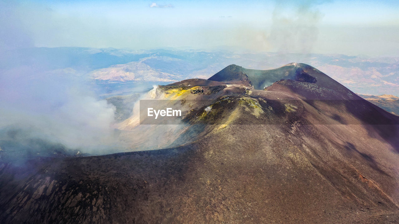 Crater etna top view from above in a panoramic aerial photo with sulphure and smoke at degassation