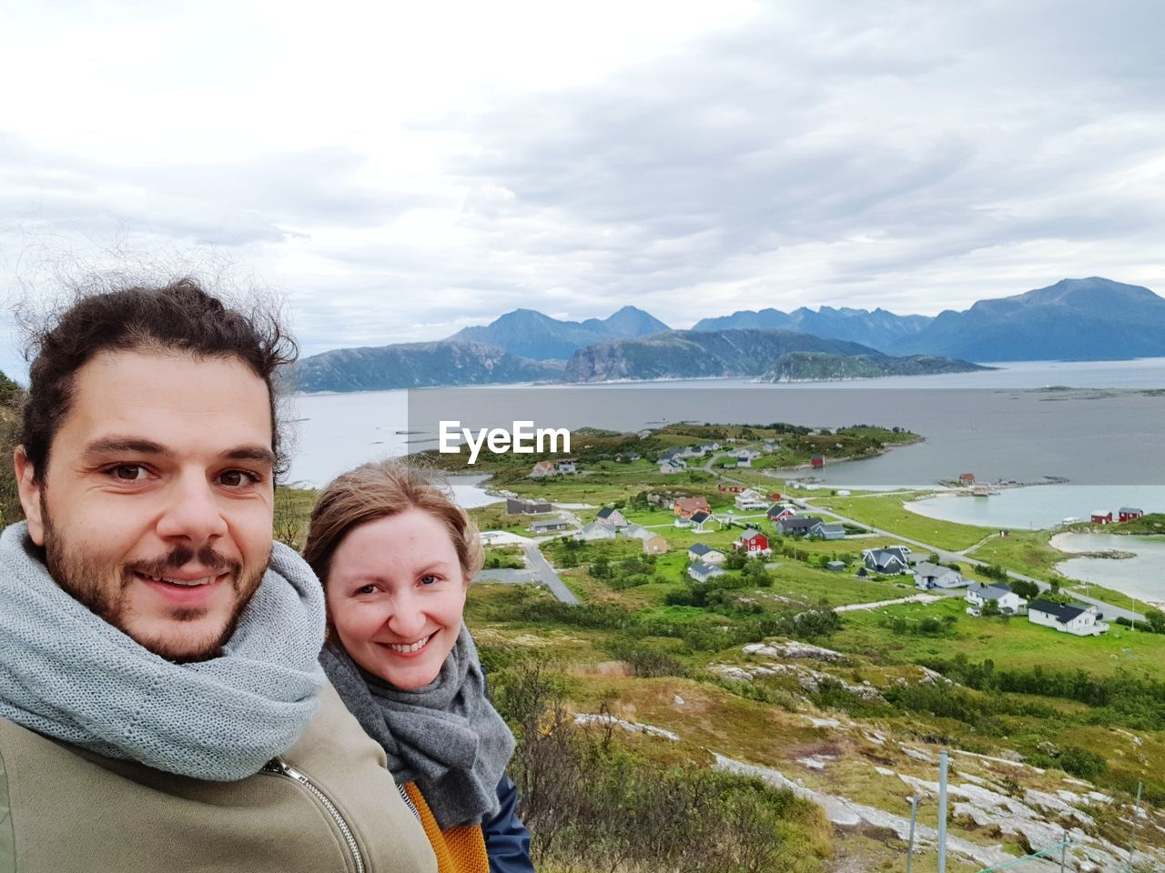 portrait, mountain, cloud - sky, looking at camera, smiling, happiness, emotion, sky, water, leisure activity, two people, real people, togetherness, beauty in nature, scenics - nature, nature, lifestyles, headshot, men, males, mountain range, positive emotion, outdoors, couple - relationship