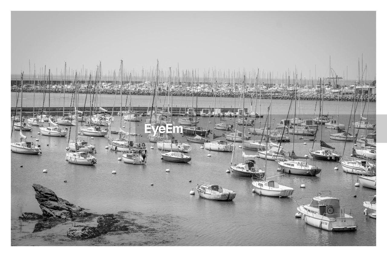 water, transportation, nautical vessel, sky, sea, transfer print, mode of transportation, nature, auto post production filter, harbor, moored, day, no people, high angle view, architecture, sailboat, outdoors, marina, building exterior, yacht, port, anchored