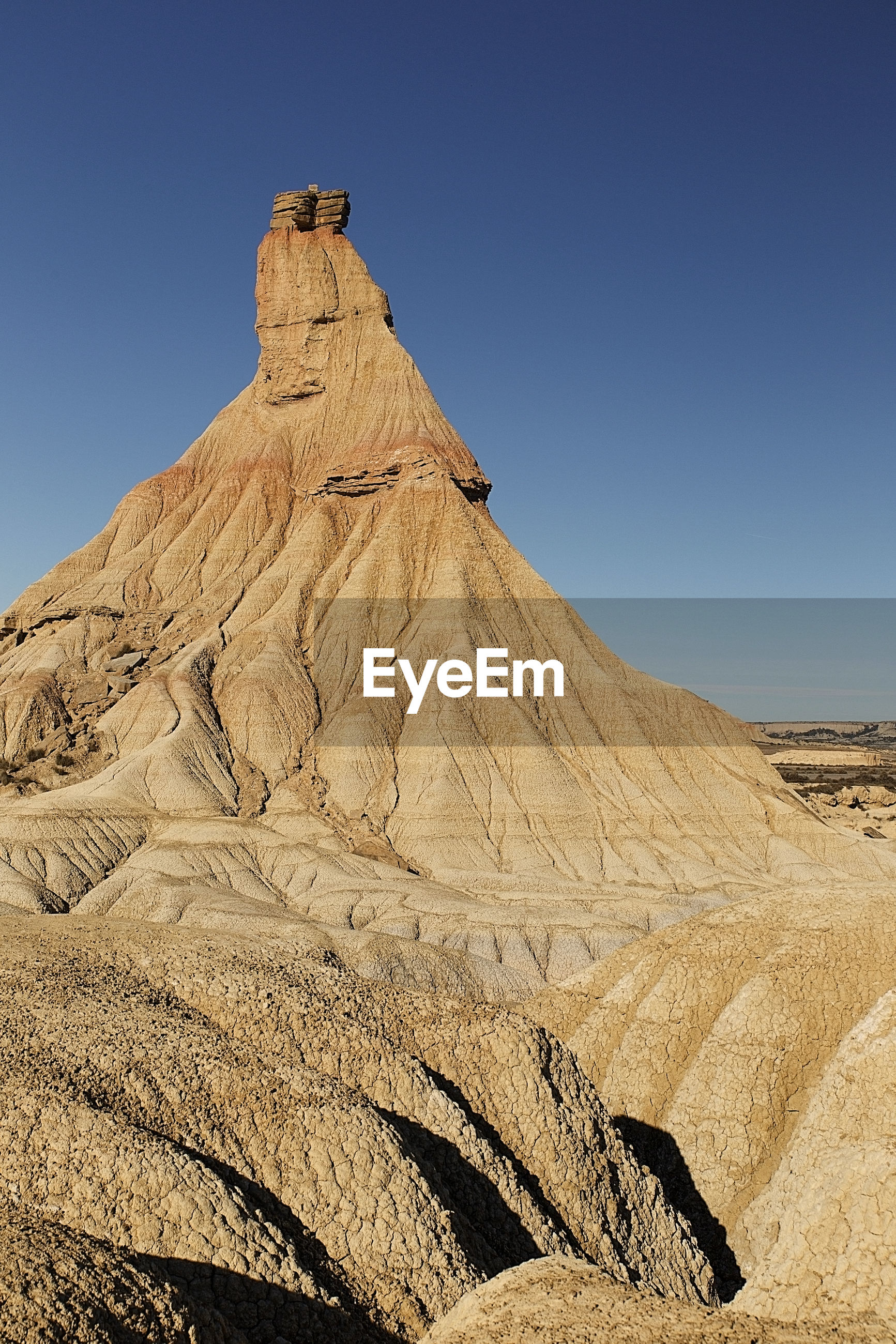 ROCK FORMATIONS ON DESERT AGAINST CLEAR BLUE SKY