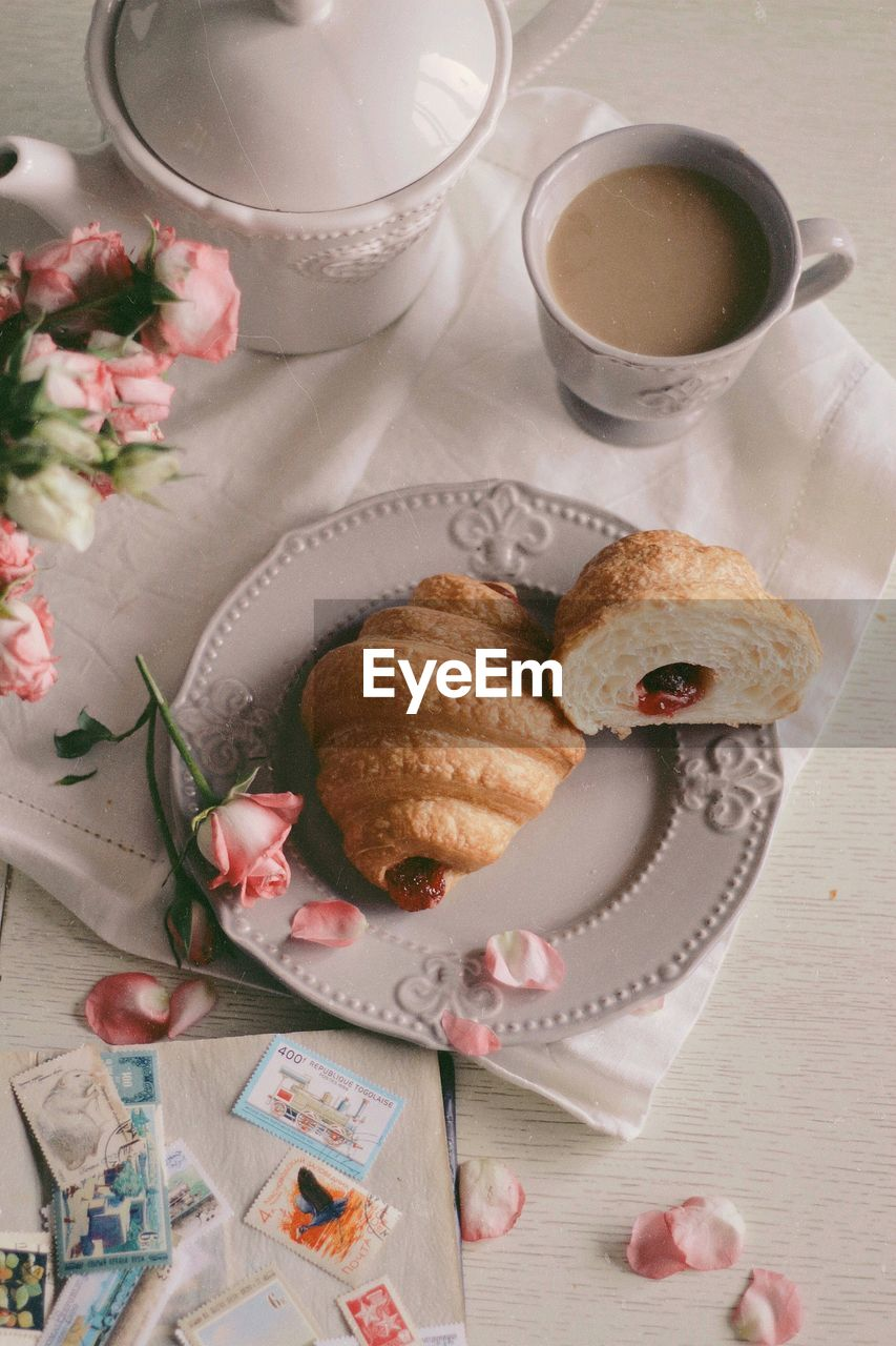 High angle view of croissants by coffee cup in plate