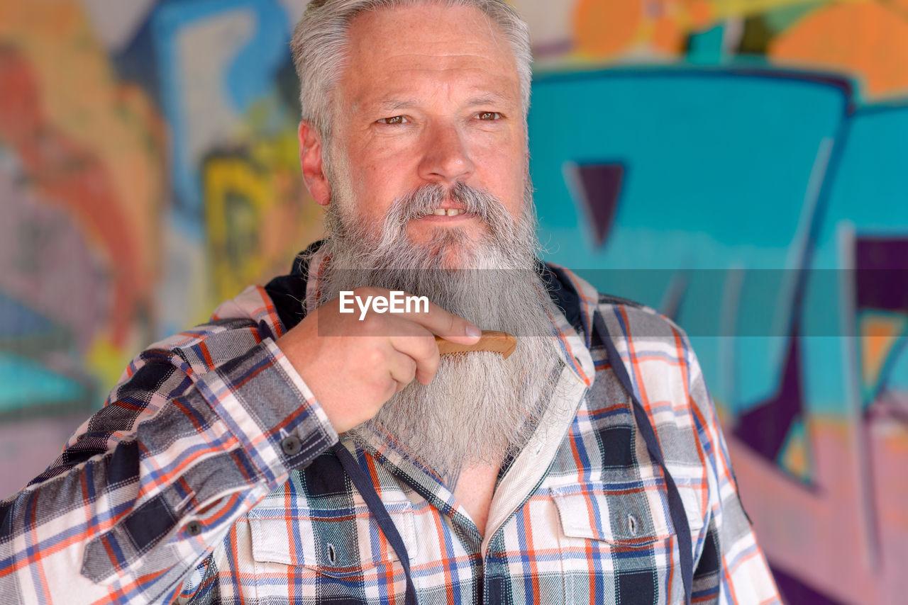 Portrait Of Bearded Man Combing Beard Against Graffiti Wall