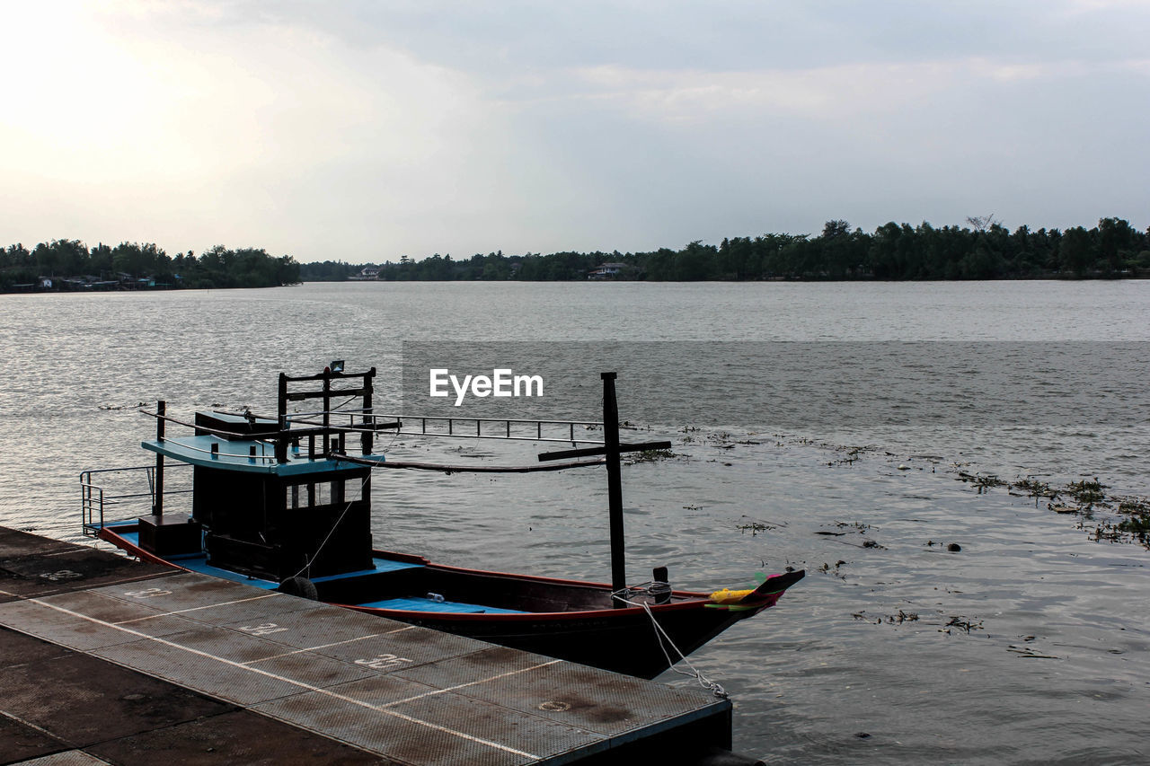 water, nautical vessel, sky, transportation, mode of transportation, tranquility, no people, moored, nature, tranquil scene, beauty in nature, lake, scenics - nature, day, cloud - sky, outdoors, tree, non-urban scene, plant, rowboat, anchored