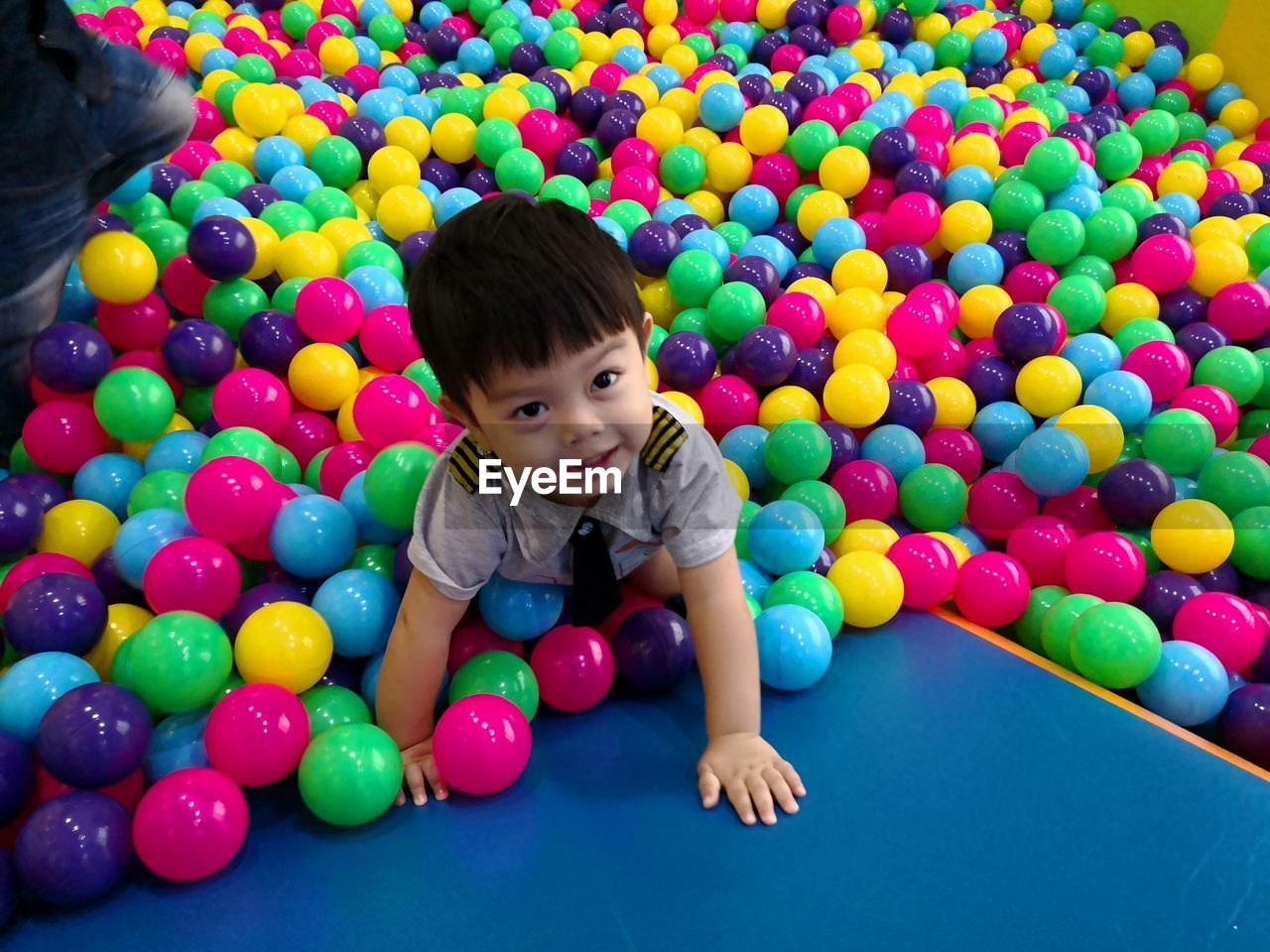 Cute smiling boy looking away while playing with colorful balls