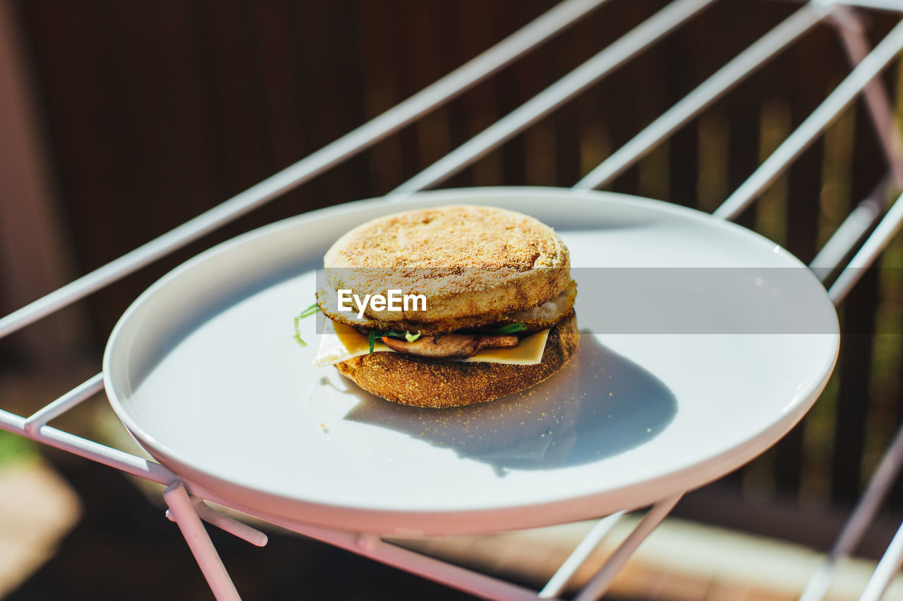 Close-Up Of Burger In Plate On Clothes Rack