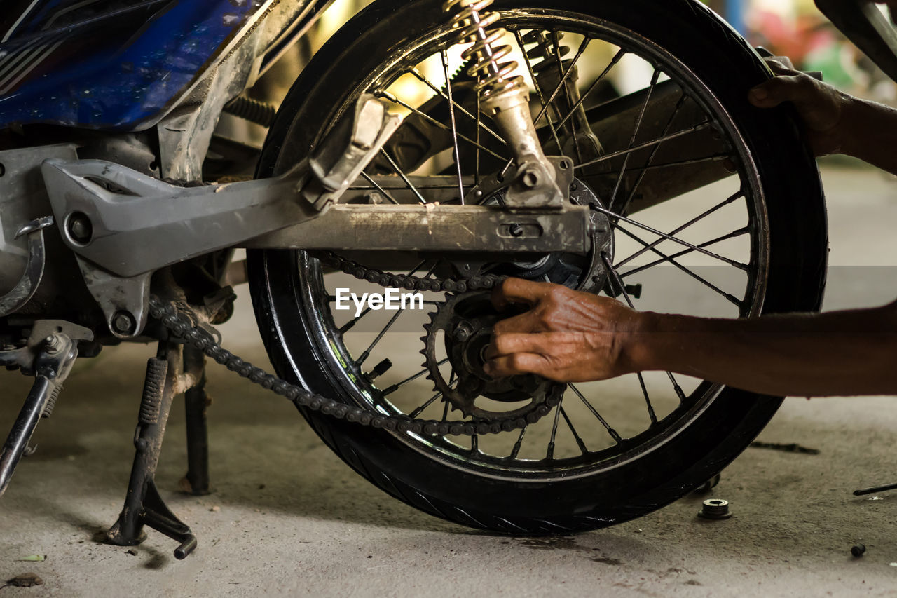wheel, transportation, bicycle, tire, mode of transportation, land vehicle, one person, real people, spoke, day, outdoors, travel, close-up, human body part, focus on foreground, stationary, metal, city, repairing, mechanic