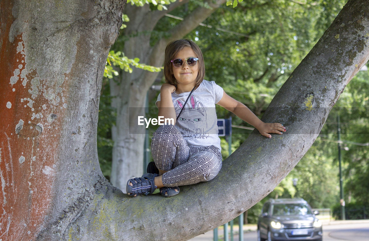 childhood, one person, tree, child, casual clothing, glasses, tree trunk, girls, women, trunk, looking at camera, full length, females, portrait, front view, plant, fashion, leisure activity, innocence, day, outdoors, human arm, hairstyle