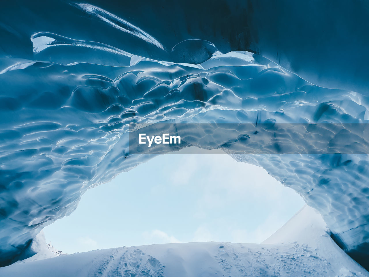 Aerial view of frozen sea by mountain against sky