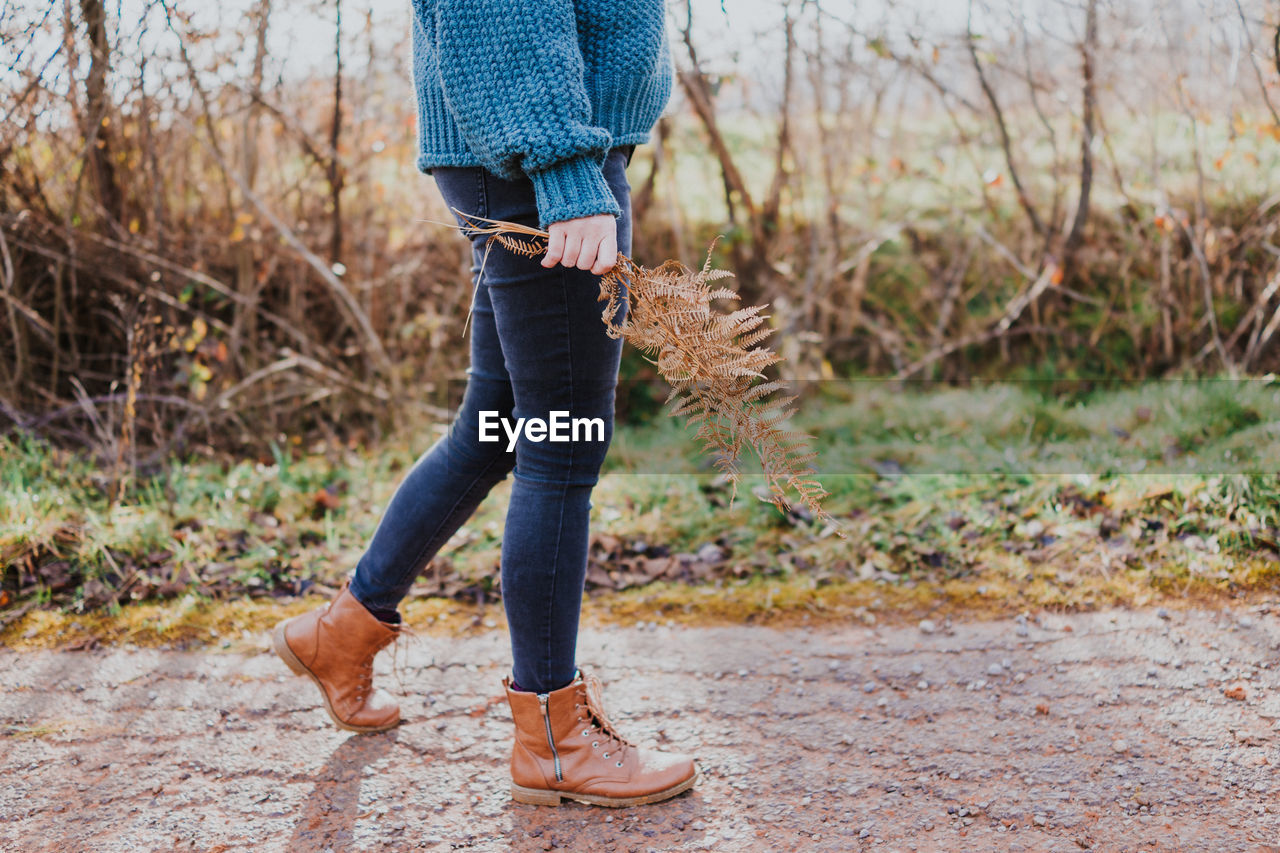 one person, low section, casual clothing, human leg, real people, human body part, jeans, day, body part, lifestyles, leisure activity, land, nature, shoe, standing, plant, walking, focus on foreground, outdoors, human limb, human foot