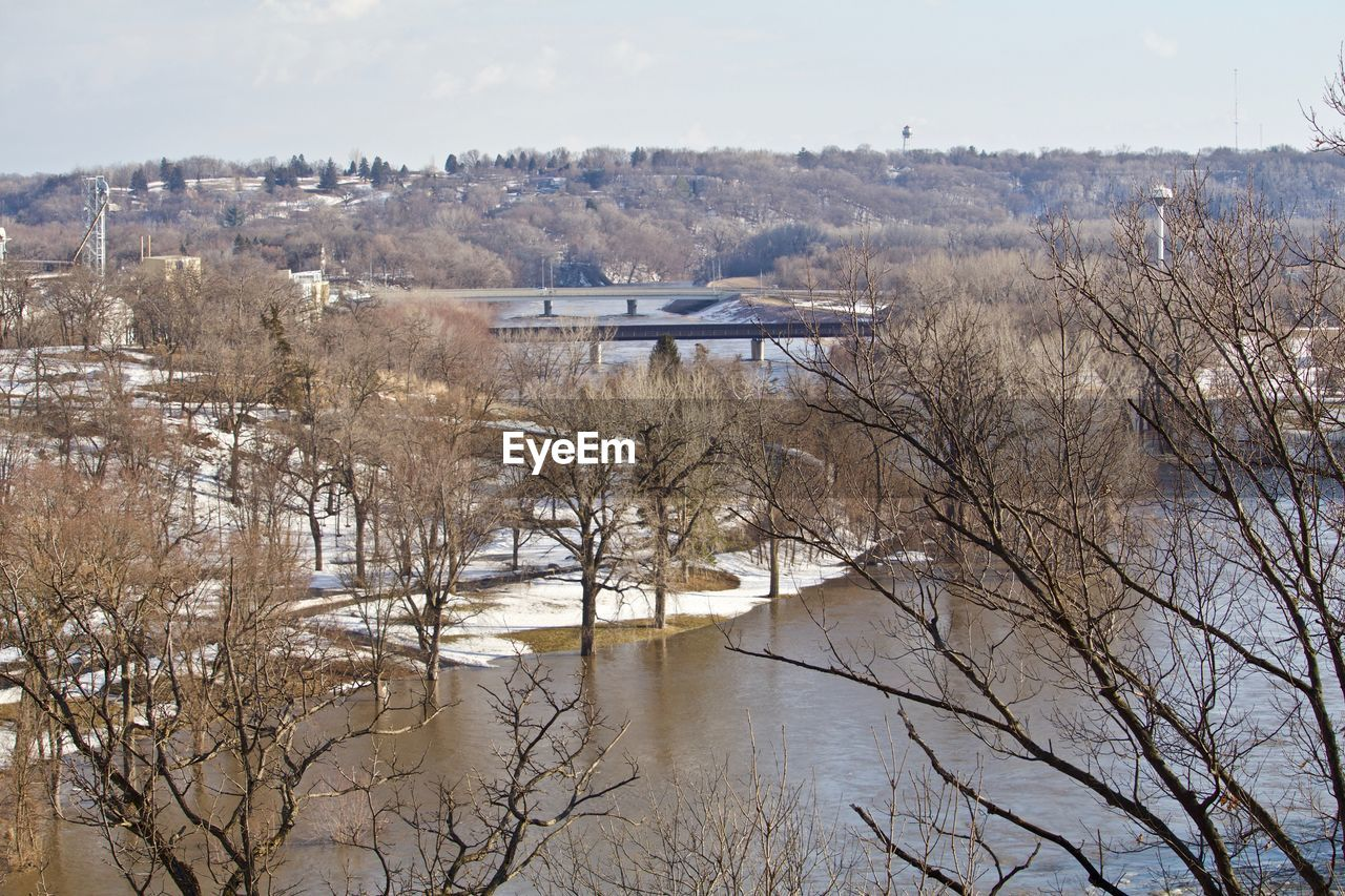 SCENIC VIEW OF RIVER BY SNOW COVERED TREES AGAINST SKY