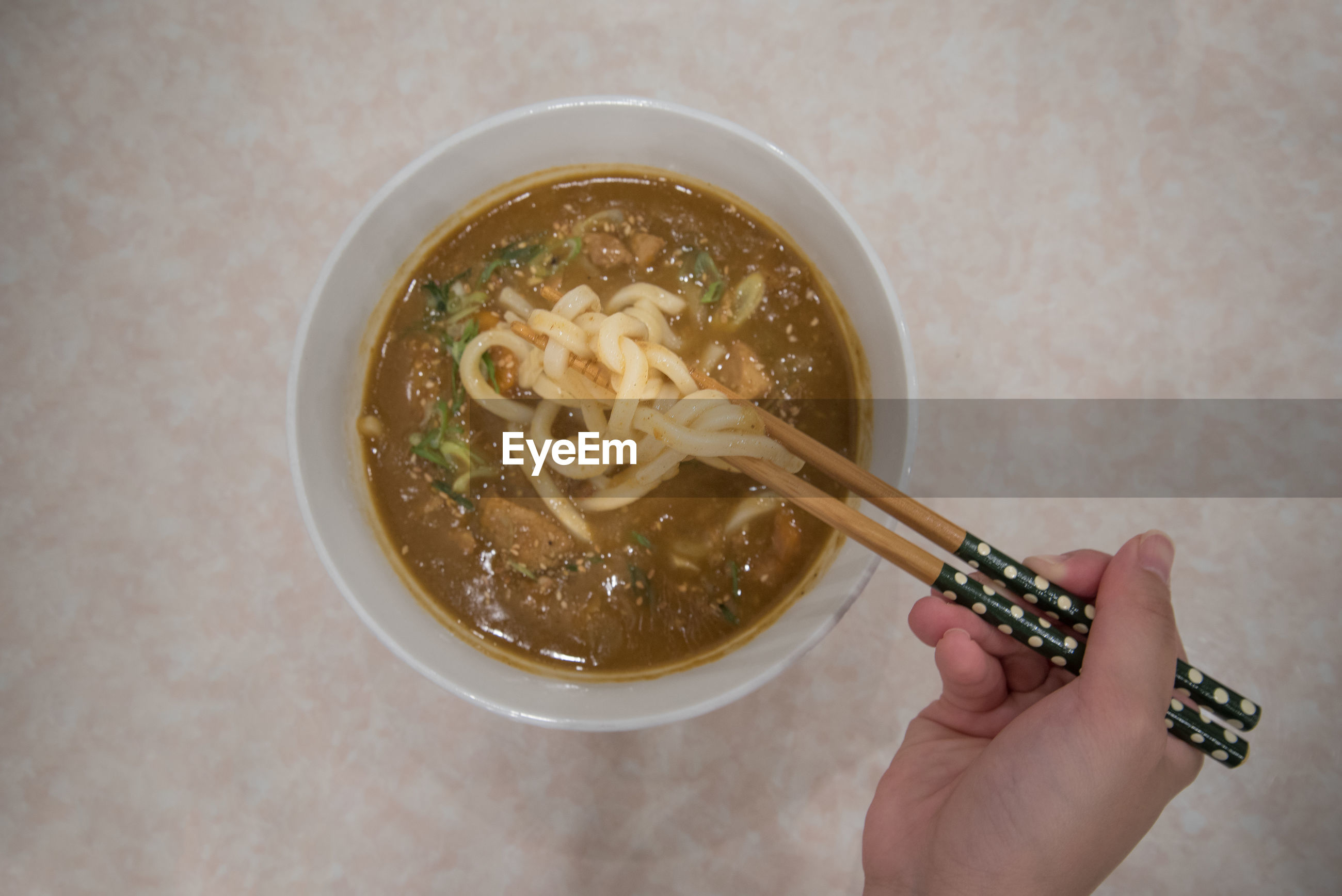 Cropped hand having noodles in bowl