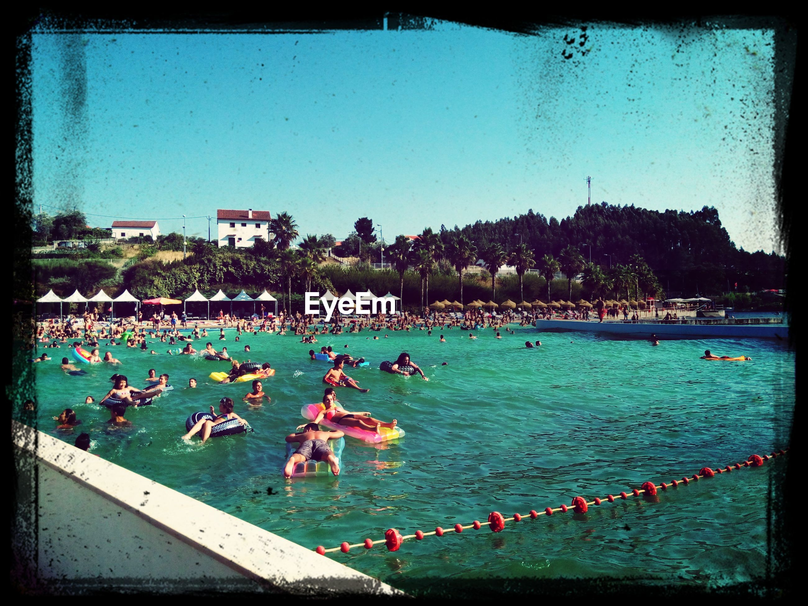 water, transfer print, sea, auto post production filter, large group of people, blue, clear sky, beach, built structure, building exterior, tree, architecture, incidental people, sky, high angle view, vacations, outdoors, nature, river