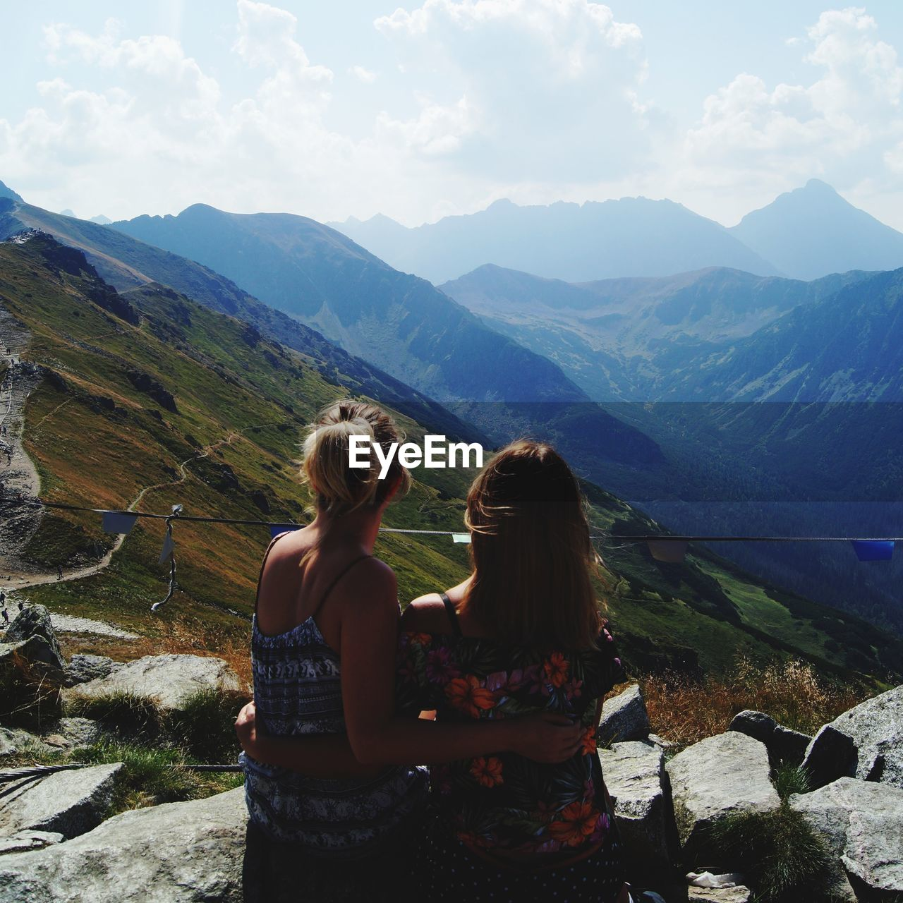 mountain, leisure activity, beauty in nature, real people, scenics - nature, mountain range, lifestyles, two people, tranquil scene, sky, tranquility, women, non-urban scene, rear view, togetherness, nature, cloud - sky, child, sitting, day, outdoors, looking at view