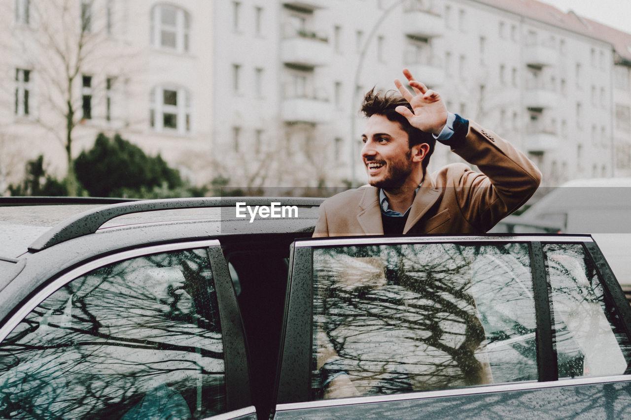Smiling Young Man Entering Car
