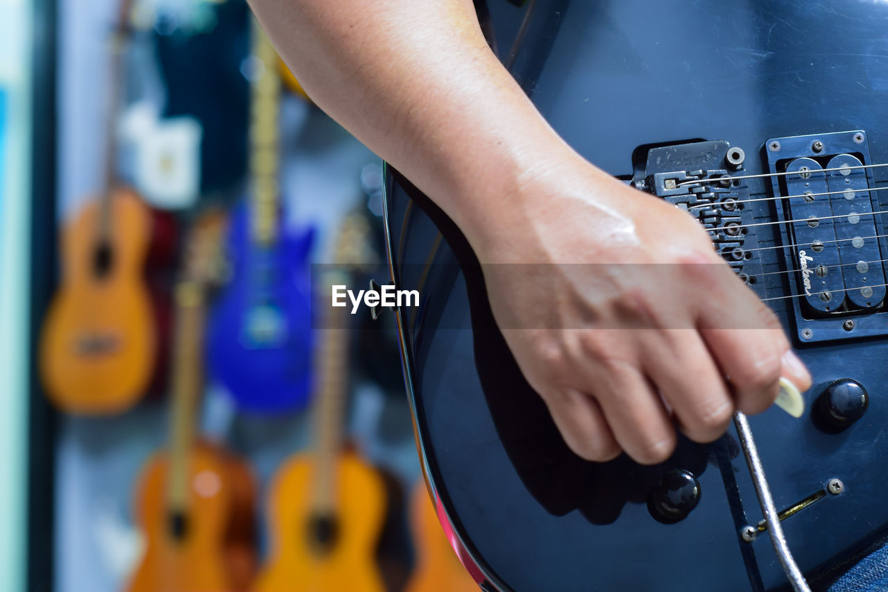 Cropped Image Of Musician Playing Guitar At Store