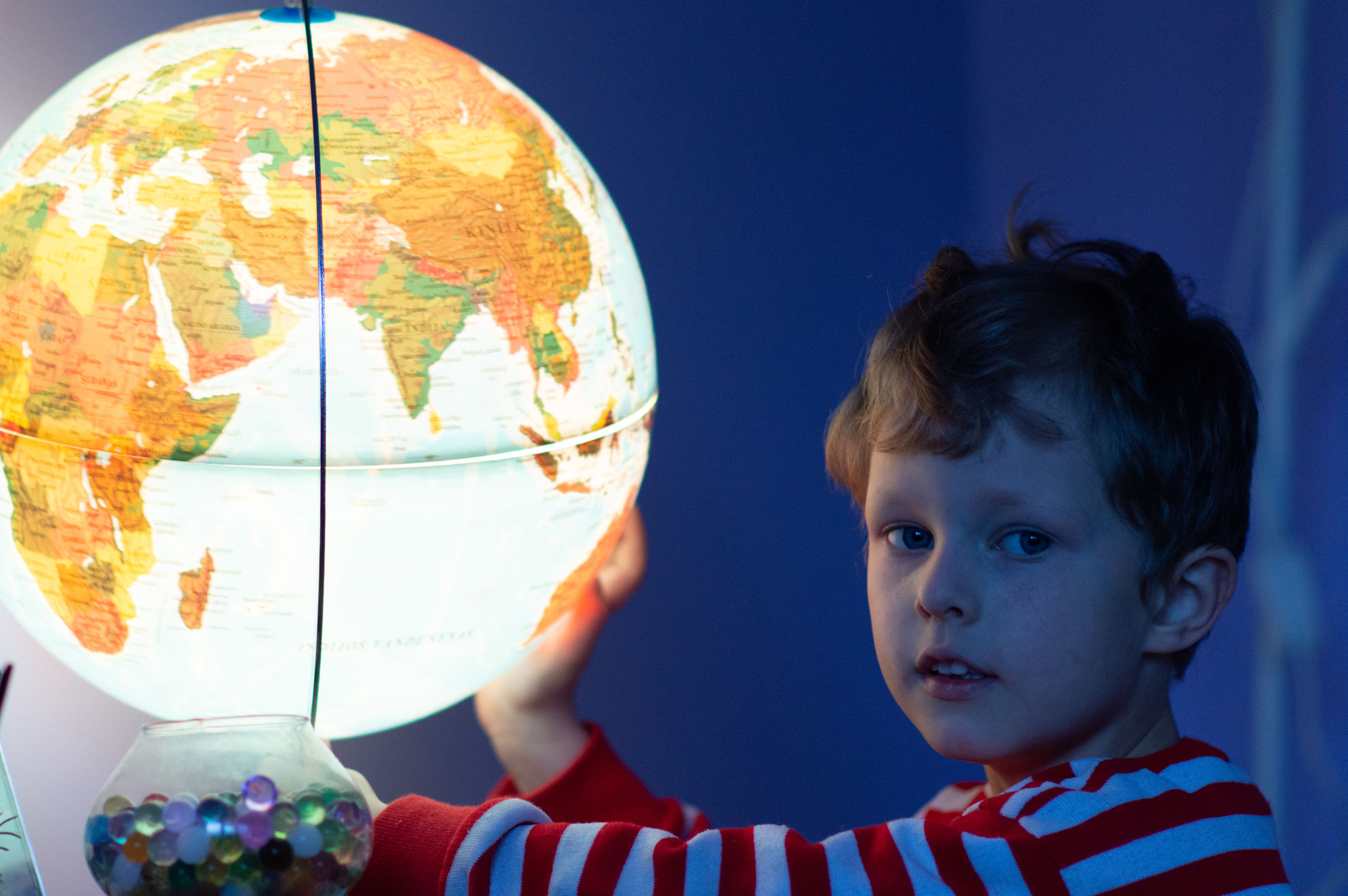 Side view portrait of cute boy with illuminated globe at home