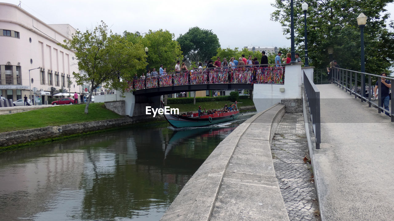 built structure, architecture, water, plant, building exterior, canal, tree, nature, bridge, transportation, nautical vessel, reflection, connection, incidental people, day, city, sky, group of people, large group of people, outdoors, footbridge