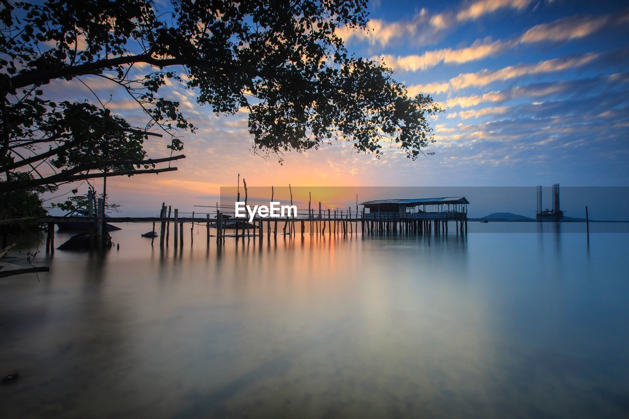 sunset, water, sky, nature, scenics, orange color, beauty in nature, silhouette, sea, tranquil scene, tranquility, tree, built structure, cloud - sky, outdoors, no people, horizon over water, architecture, day