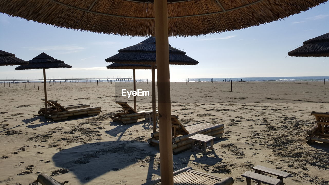 beach, sand, beach umbrella, sea, nature, thatched roof, water, shore, beauty in nature, tranquility, tranquil scene, summer, vacations, scenics, protection, horizon over water, canopy, outdoors, sun lounger, day, relaxation, shelter, sky, no people