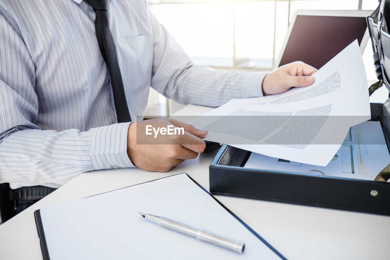 Midsection of businessman analyzing data on desk