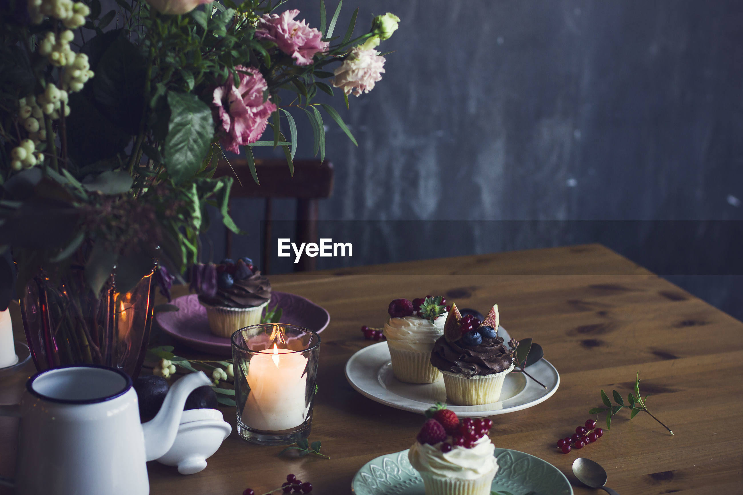 Flower vase and cup cakes in plates on table