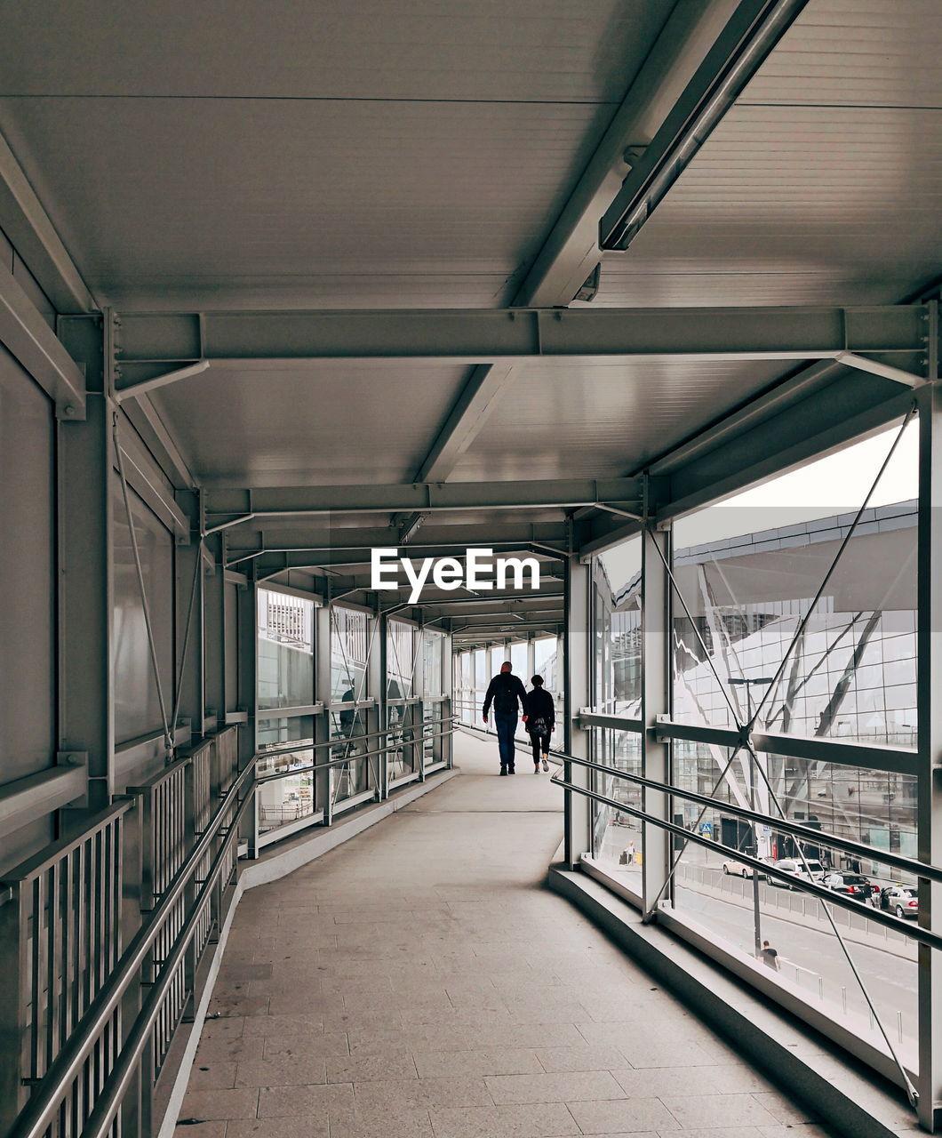 Rear View Of Couple Walking On Footbridge