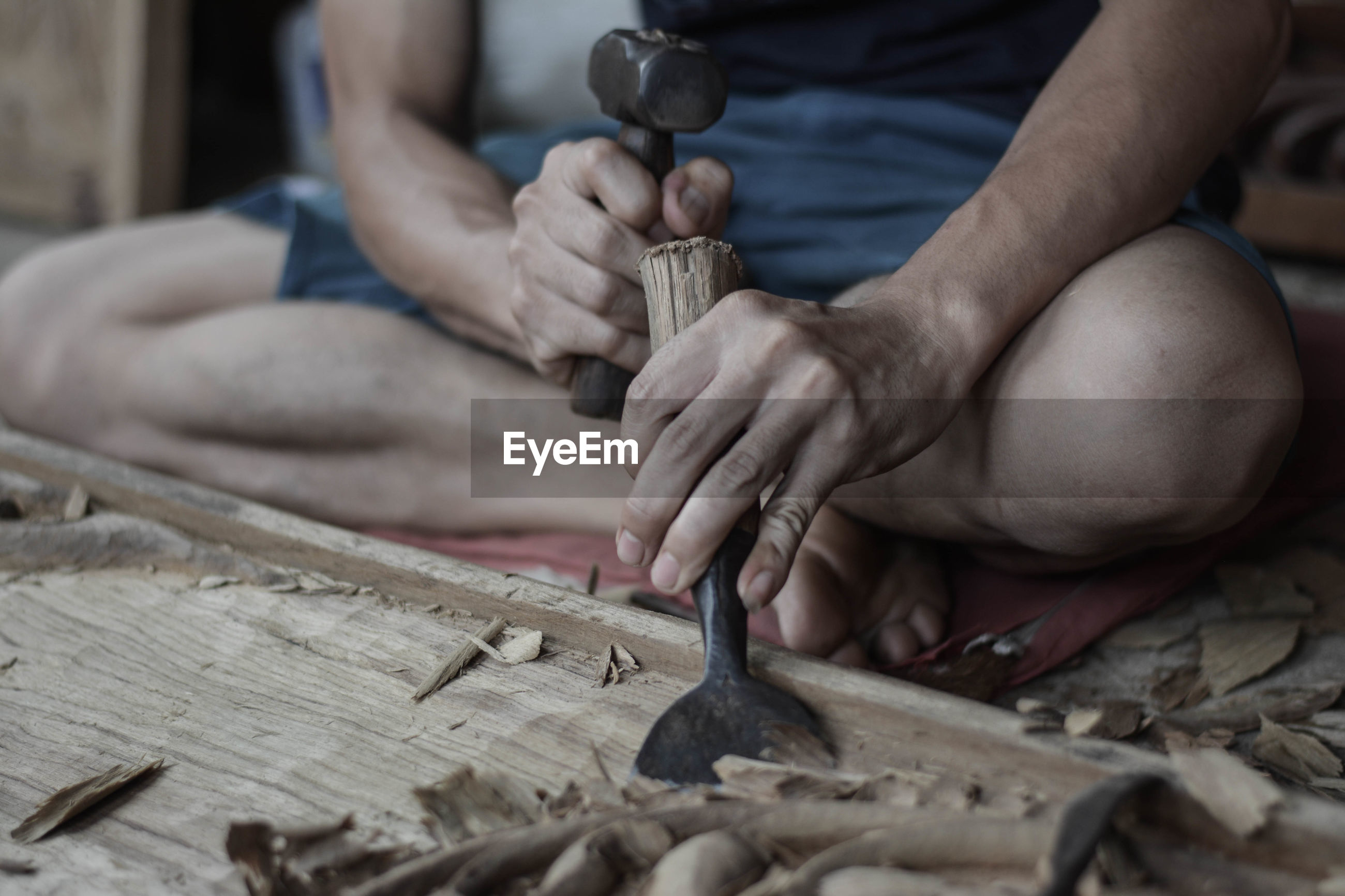 Low section of carpenter working in carpentry workshop