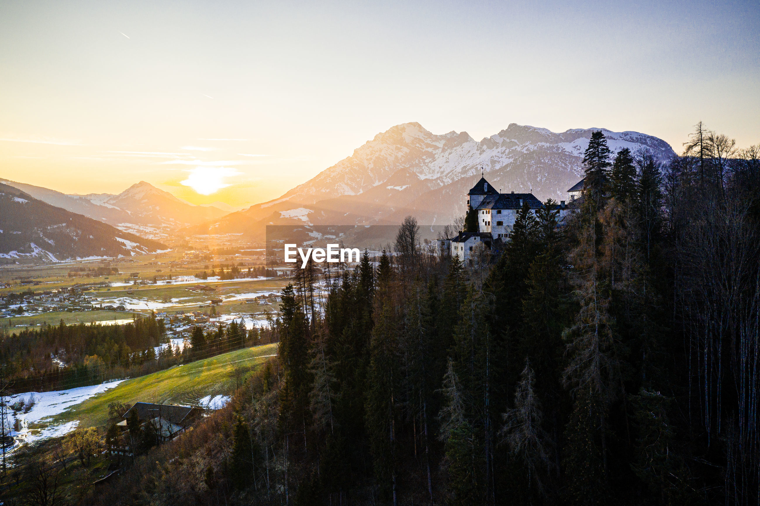 Scenic view of snowcapped mountains against sky during sunset with a castle in the voreground