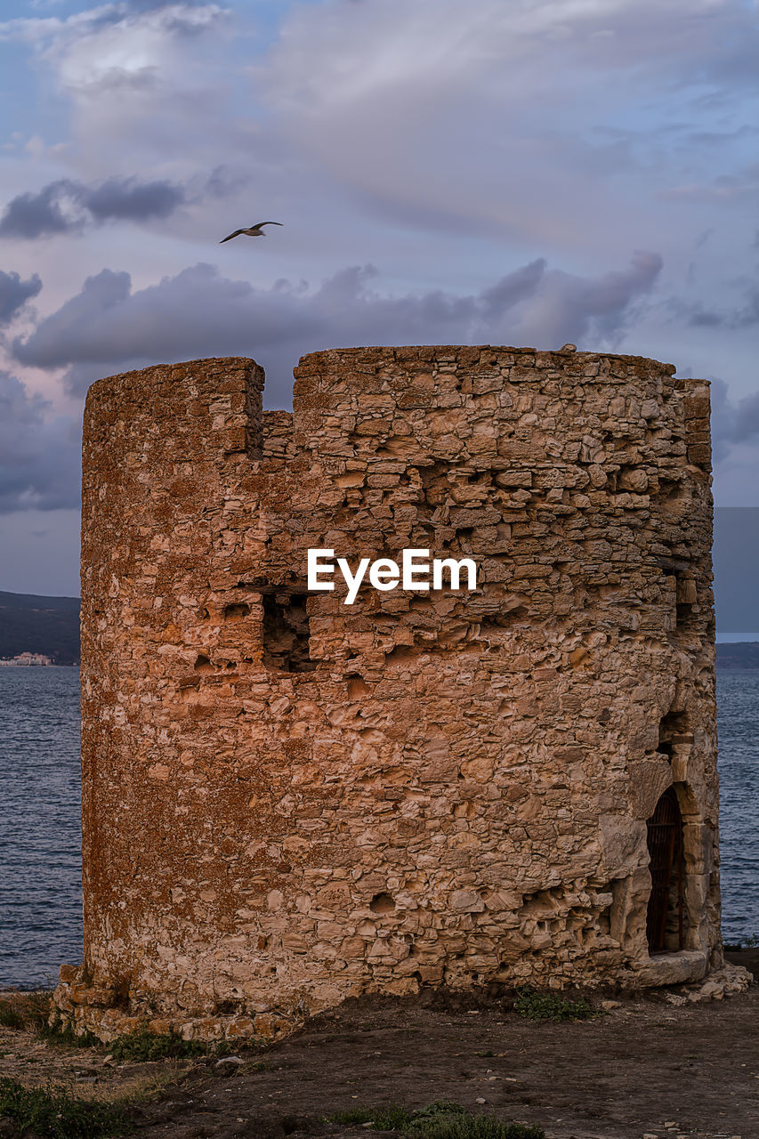 water, sea, architecture, cloud - sky, built structure, nature, history, sky, the past, no people, solid, old, day, land, scenics - nature, outdoors, tranquility, rock, tranquil scene, ruined