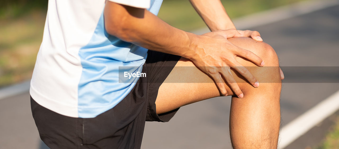 Midsection of man touching knee in pain while standing on street