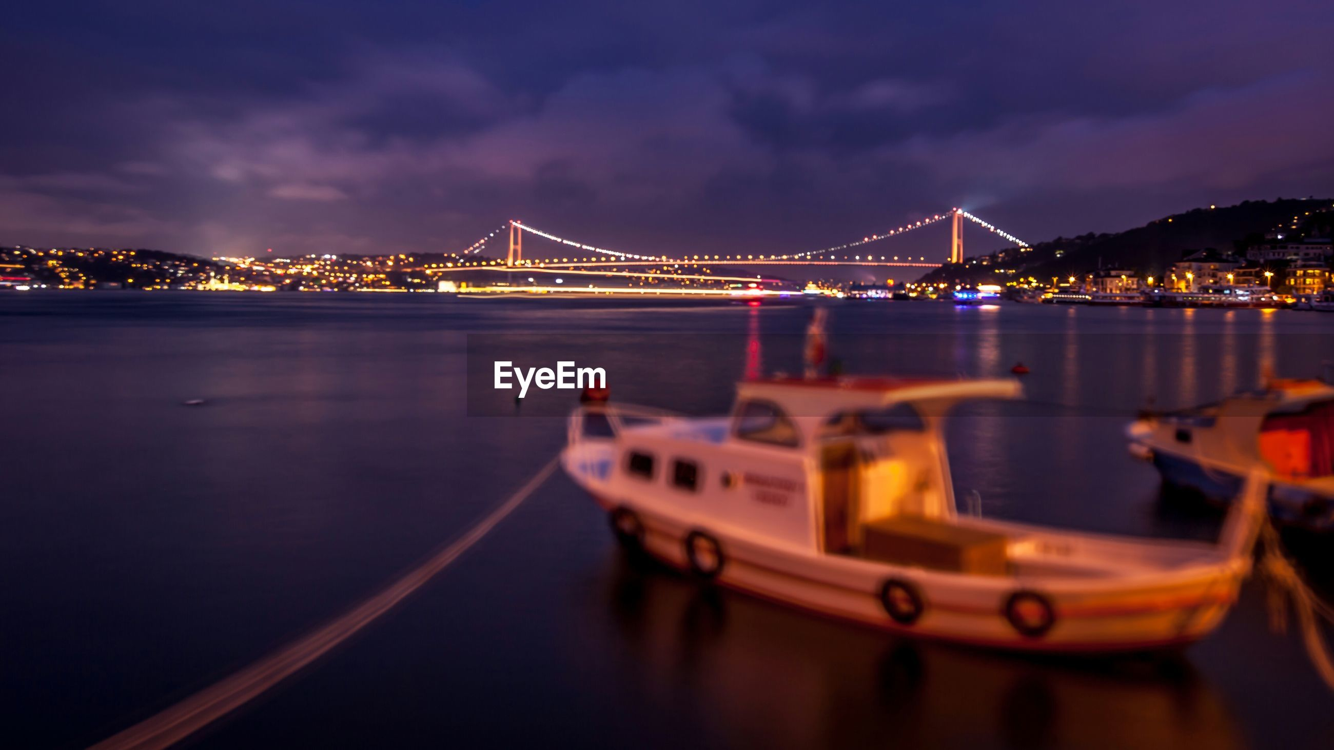 Nautical vessel moored on river by illuminated city and bosphorus bridge against sky
