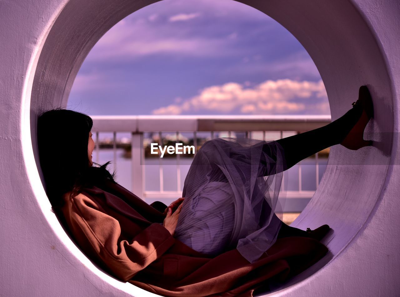 Side view of woman relaxing on circle shape structure against sky during sunset