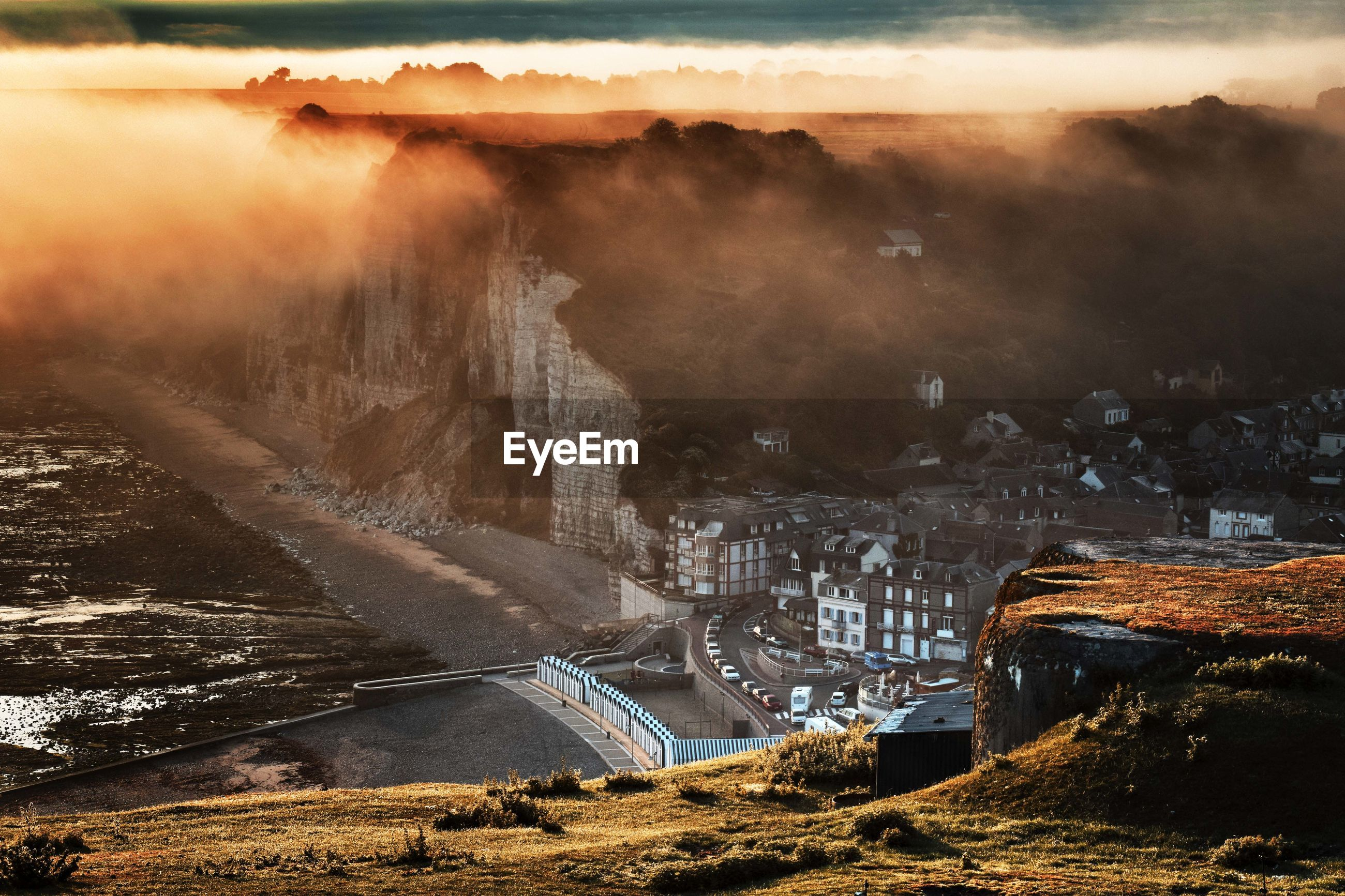 High angle view of buildings in town by mountain during foggy sunset
