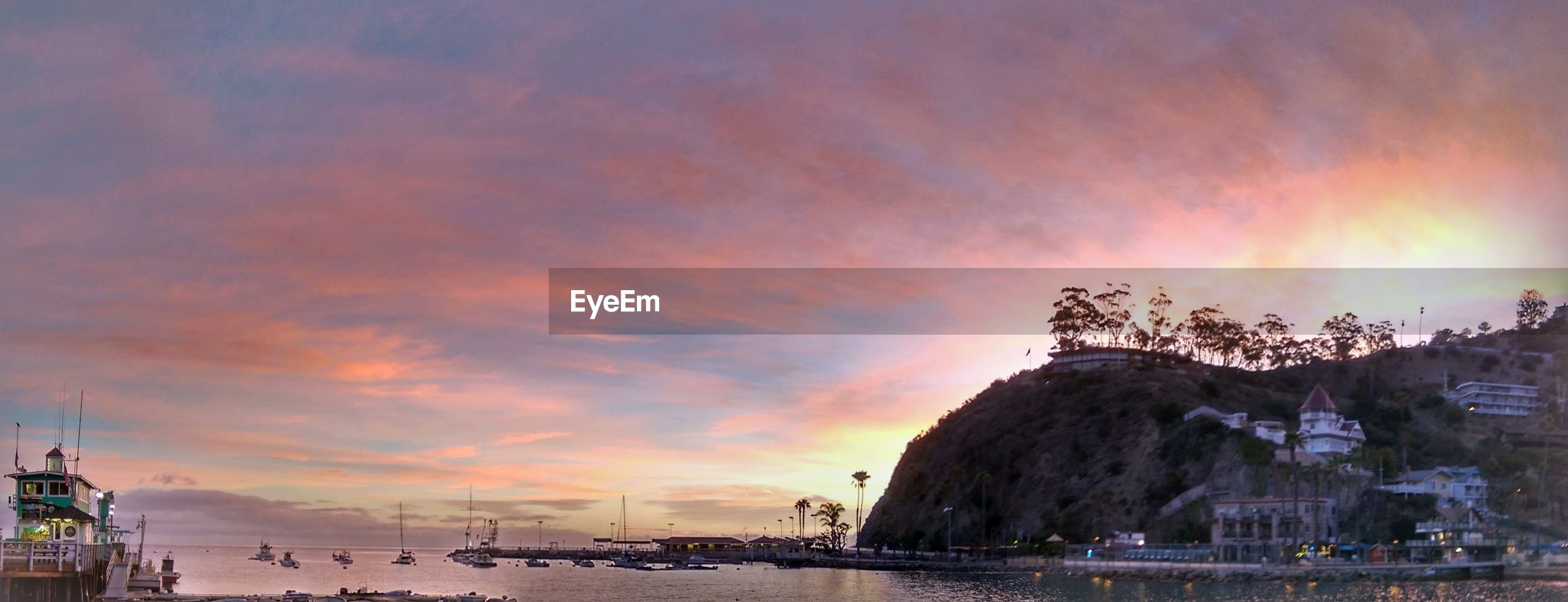 PANORAMIC VIEW OF SEA AGAINST BUILDINGS AT SUNSET