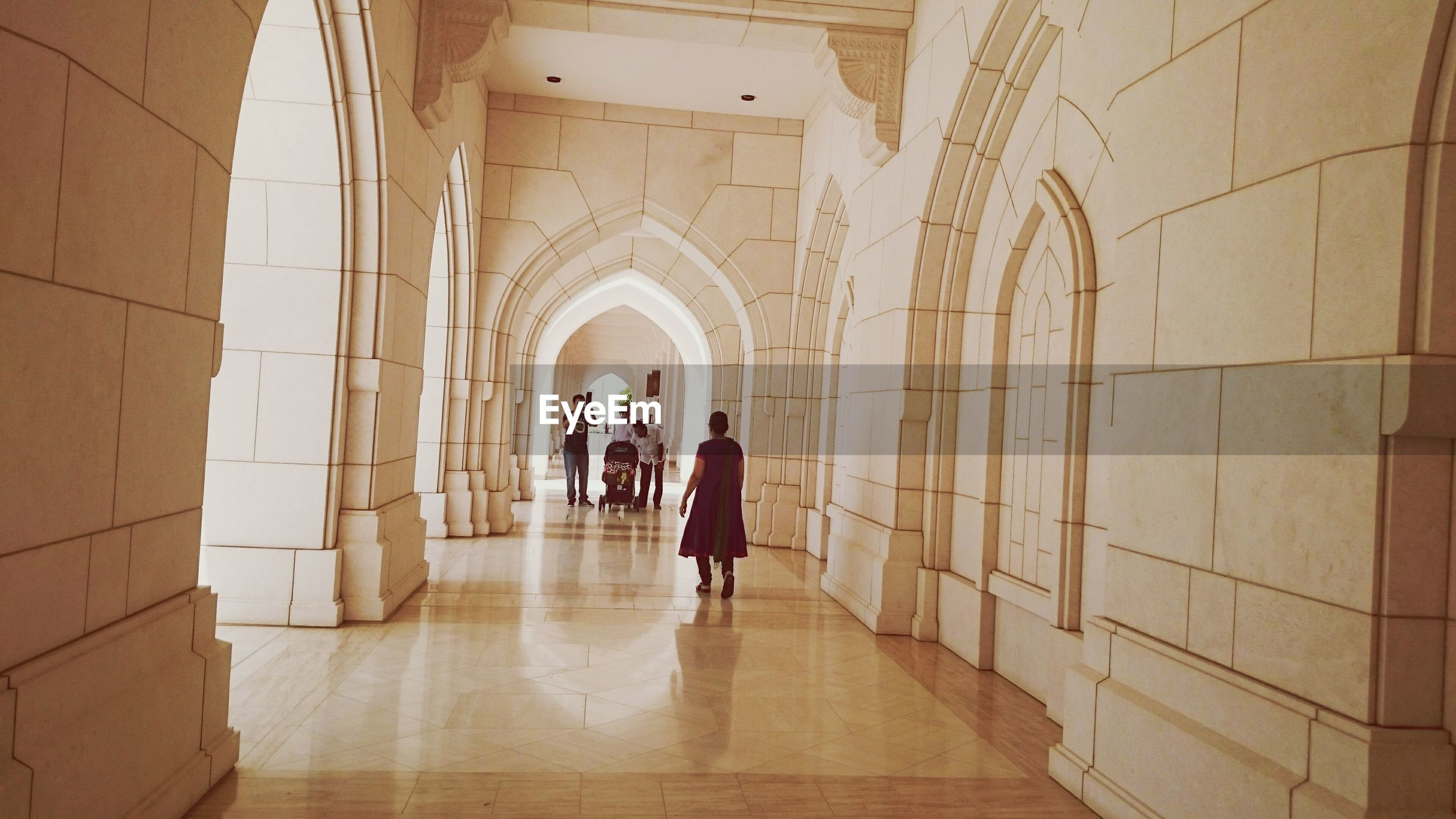 indoors, architecture, arch, full length, built structure, lifestyles, walking, leisure activity, rear view, men, person, wall - building feature, corridor, standing, the way forward, flooring, tiled floor, casual clothing