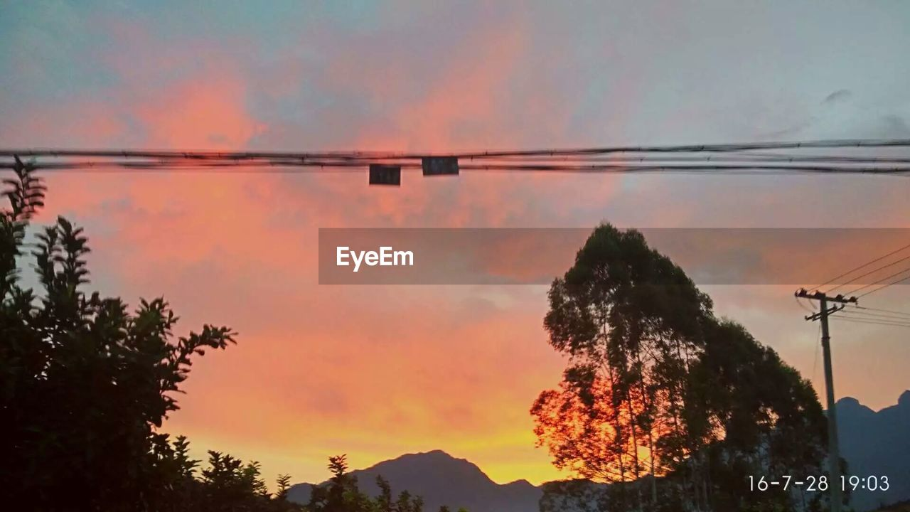 sunset, orange color, tree, silhouette, nature, connection, sky, beauty in nature, cable, no people, outdoors, cloud - sky, low angle view, scenics, tranquil scene, electricity pylon, tranquility, mountain, technology, day