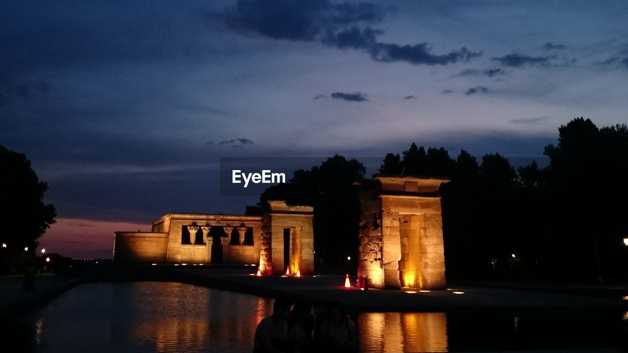 Illuminated Temple Of Debod By River Against Sky At Dusk