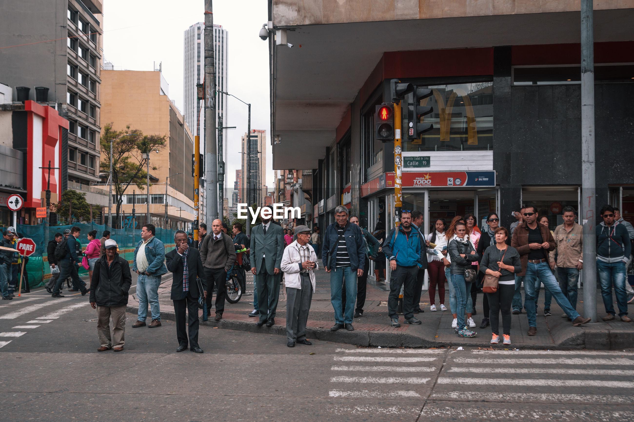 GROUP OF PEOPLE WALKING ON CITY STREET
