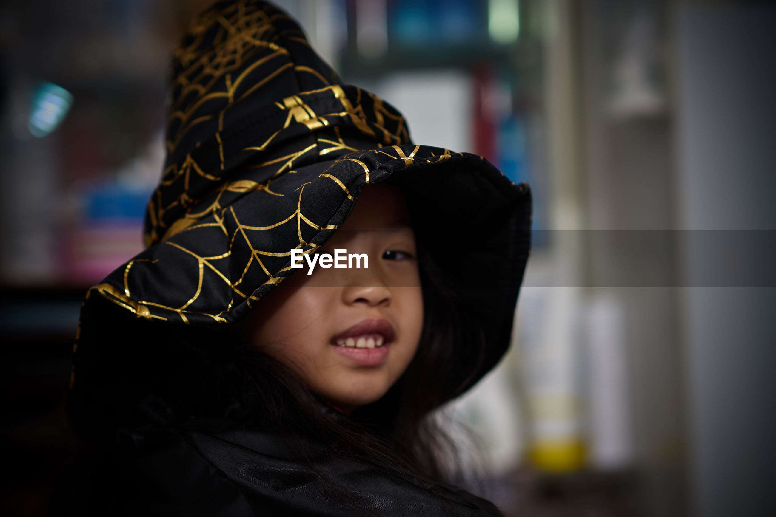 Portrait of girl wearing witch hat at home