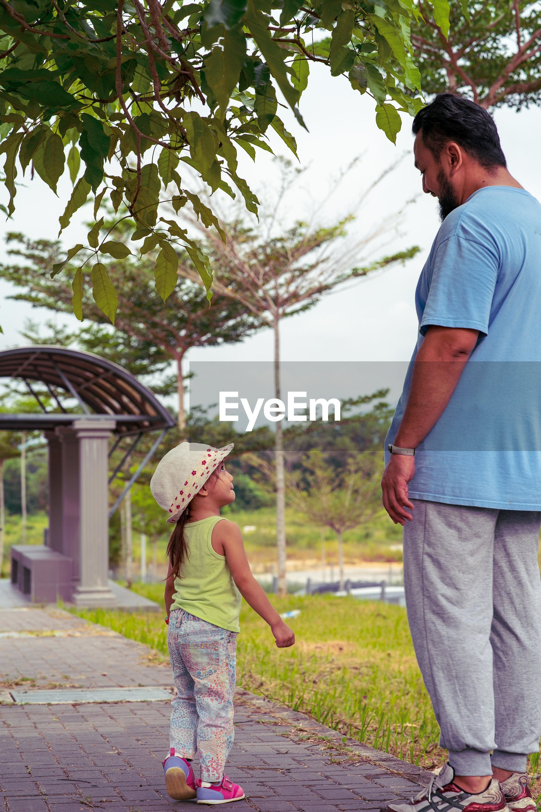 Father with daughter standing on footpath in park