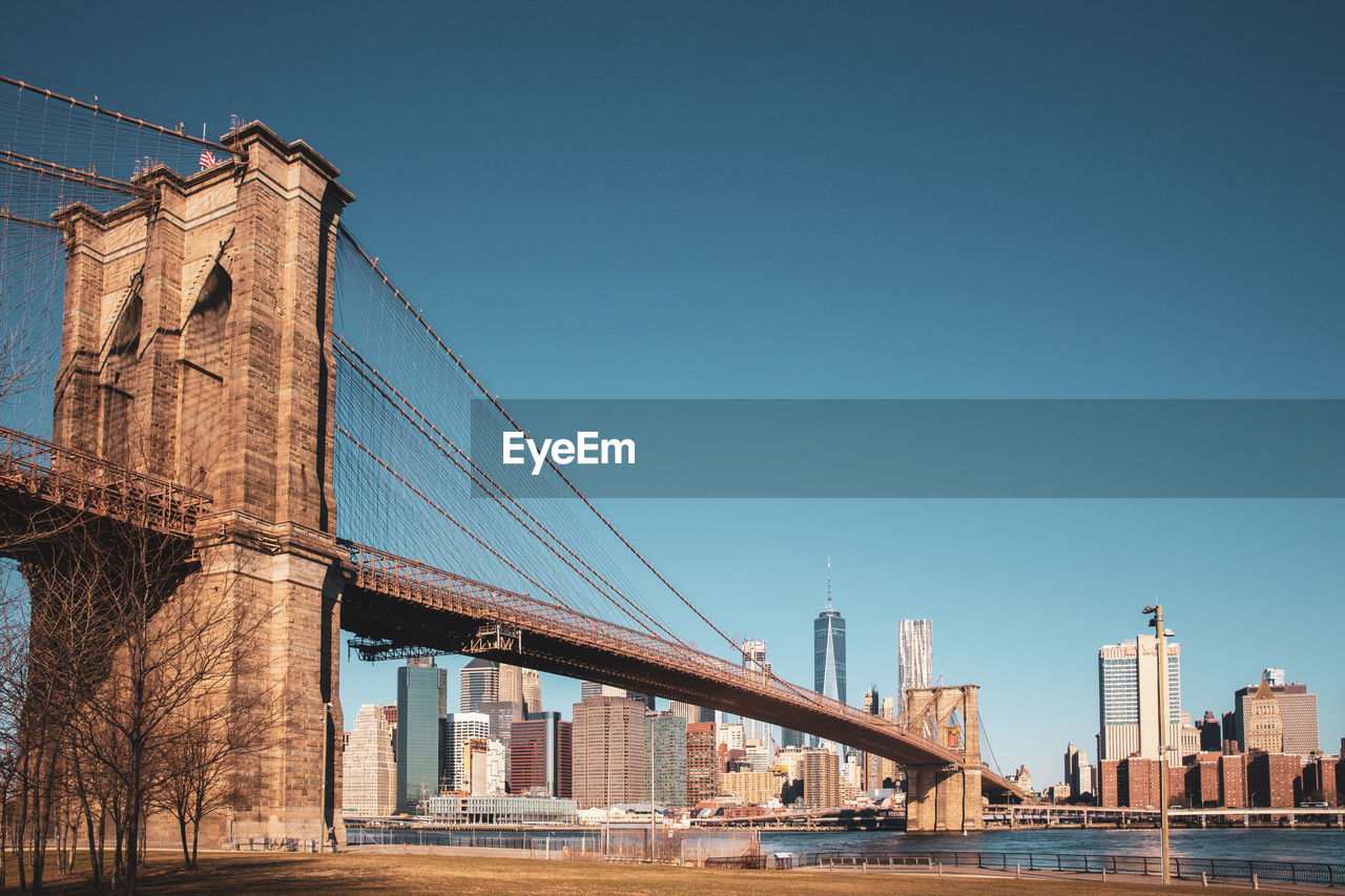 Low Angle View Of Brooklyn Bridge Over River Against Clear Blue Sky In City