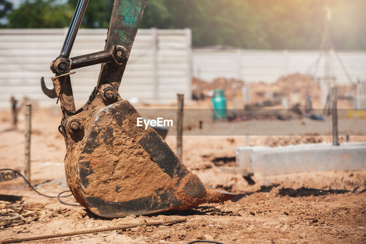 focus on foreground, day, close-up, nature, no people, land, metal, outdoors, sunlight, selective focus, old, dirt, construction site, construction industry, equipment, wood - material, rusty, hand tool, field, mud