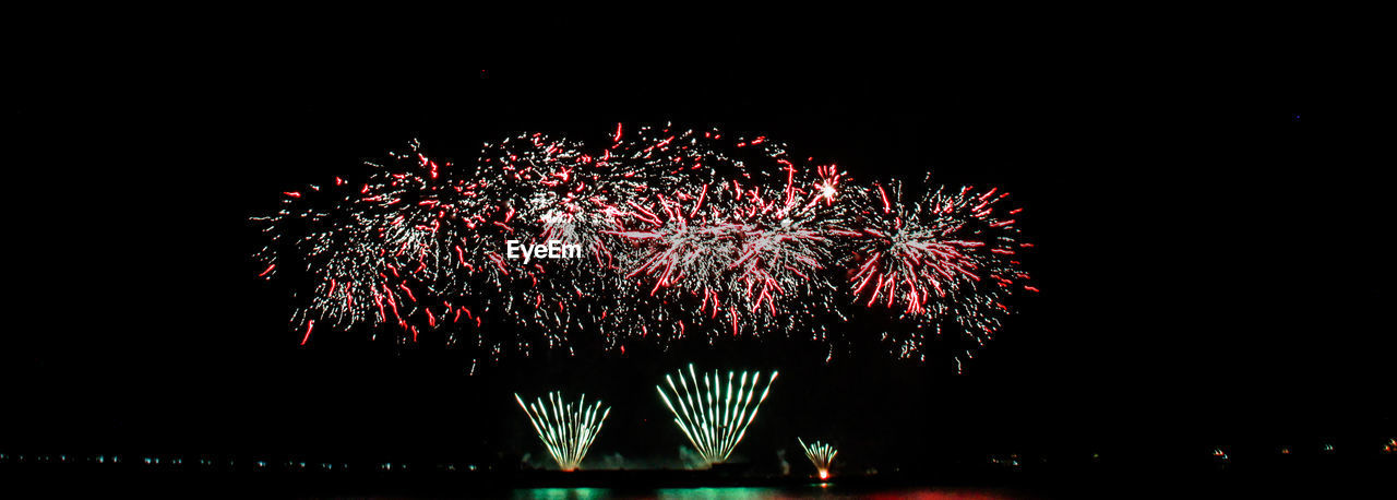 night, firework display, celebration, firework - man made object, exploding, arts culture and entertainment, illuminated, long exposure, blurred motion, event, motion, low angle view, outdoors, sky, firework, clear sky, multi colored, no people