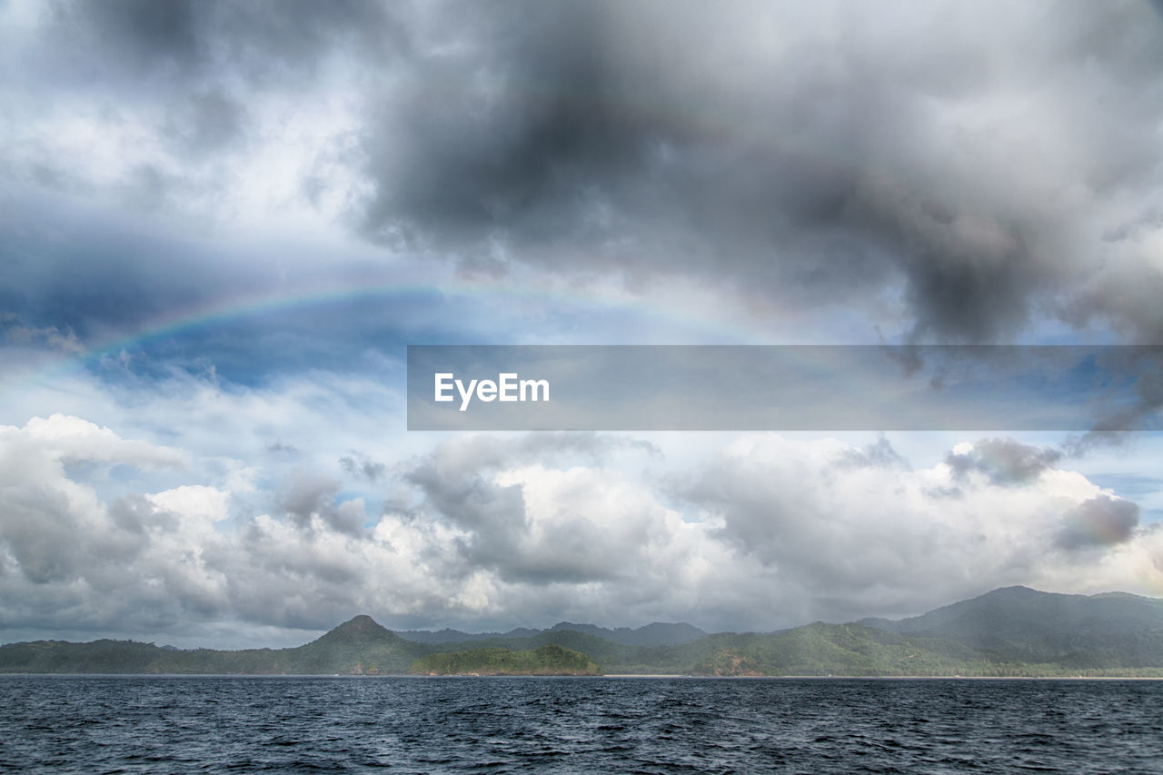 cloud - sky, sky, water, beauty in nature, scenics - nature, tranquility, tranquil scene, sea, nature, mountain, no people, waterfront, rainbow, overcast, idyllic, day, non-urban scene, storm, outdoors, ominous